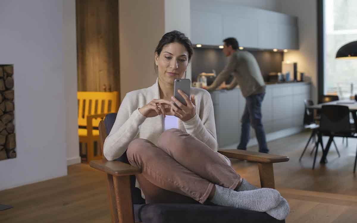 Junge Frau sitzt gemütlich auf einem Stuhl und schau in Ihr Handy