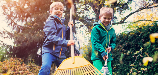 Die Kinder kehren das Laub zusammen